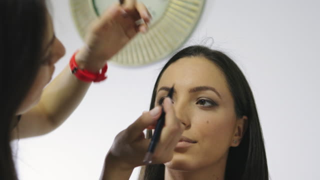 make up artist applying professional make up of beautiful young adult woman. - fashion industry stock videos & royalty-free footage