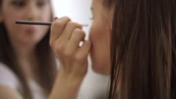Make up artist doing professional make up of young woman with freckles