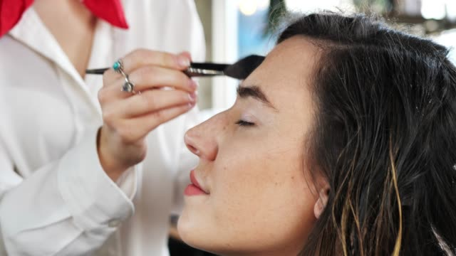make up artist putting make up on the face of client - stage make up stock videos and b-roll footage