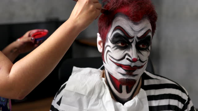 vídeos de stock, filmes e b-roll de maquiadora usando tinta de cabelo vermelho para pintar cabelo de clientes enquanto tenta recriar uma máscara de palhaço assassina assustadora para evento de halloween - fantasy