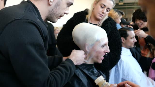 vídeos y material grabado en eventos de stock de make up artists put a calotte on models hair at han kjobenhavn backstage fashion show during milan fashion week fall/winter 2020/2021, on january 12,... - colección de la moda