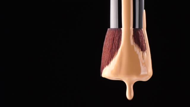 make up foundation liquid drop from brush - sfondo nero video stock e b–roll