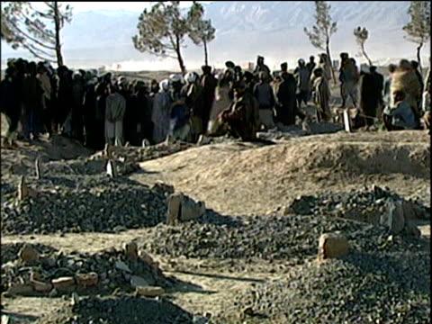Makeshift graveyard in refugee camp; Afghanistan Refugee Crisis 2001