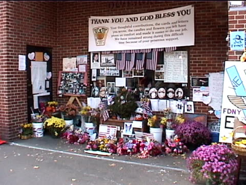 a makeshift memorial at a firehouse near ground zero in the aftermath of the 9/11 terrorist attacks in downtown manhattan - temporäre gedenkstätte stock-videos und b-roll-filmmaterial