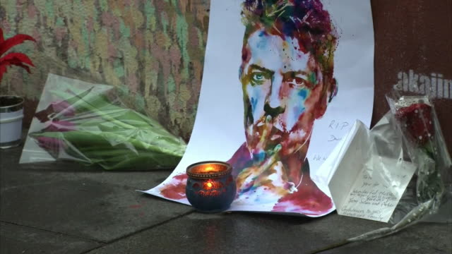 makeshift memorial of flowers, candles, and a painting of david bowie sit at the site of a david bowie mural in london, in the wake of the... - music or celebrities or fashion or film industry or film premiere or youth culture or novelty item or vacations stock videos & royalty-free footage