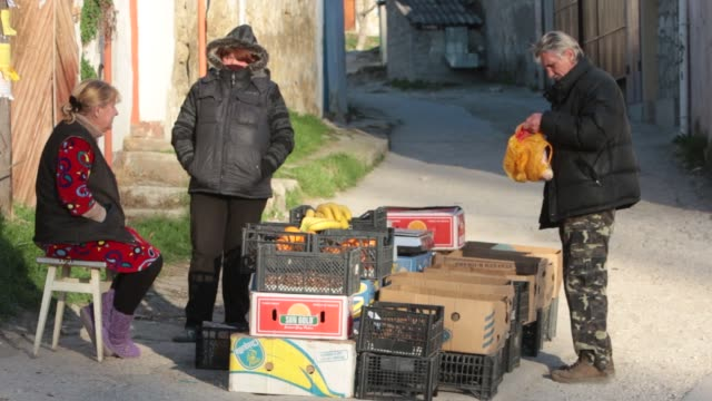 Makeshift roadside produce stand with two Crimean women selling bananas oranges potatoes and other produce Man with bag full of produce talks to women