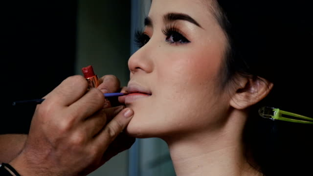 Make-up and Applying bright lipstick of Asian young woman