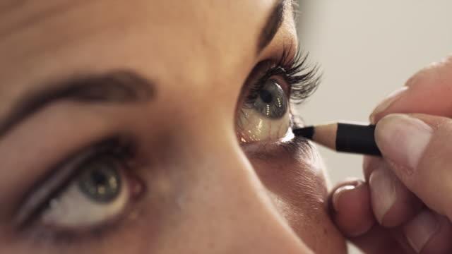 A make-up artist applies eyeliner on a model.