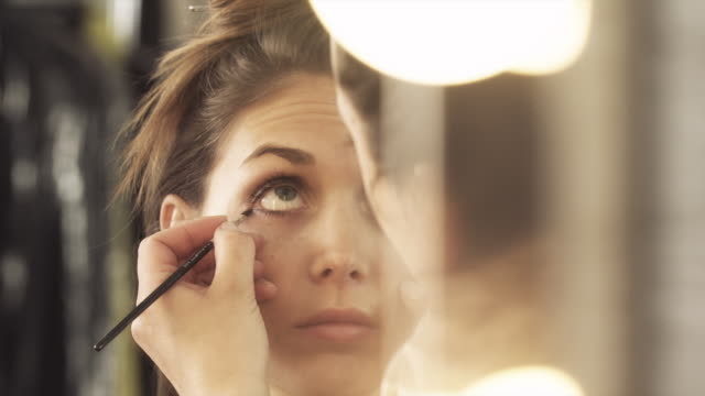 a make-up artist applies eyeliner on a model. - backstage stock videos & royalty-free footage