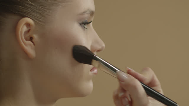 make-up artist applies makeup to a beautiful girl close-up with an eyeshadow brush. - blusher stock videos & royalty-free footage
