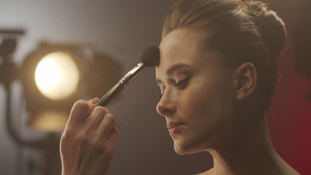 メイクアップアーティストは、セット上の女優に粉末を適用します - マスカラ点の映像素材/bロール