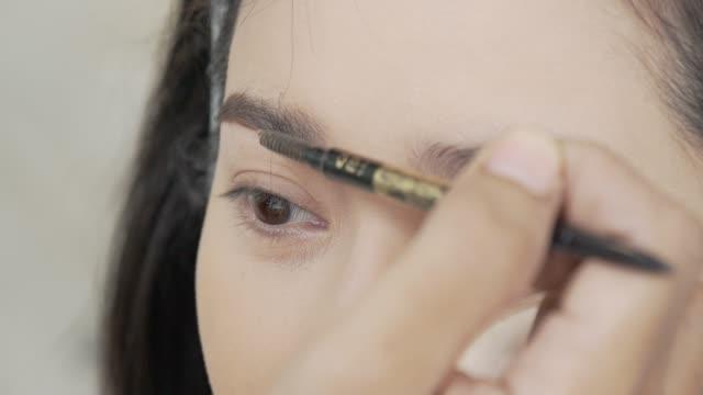 Makeup artist applying a Mascara on asian model eyebrow