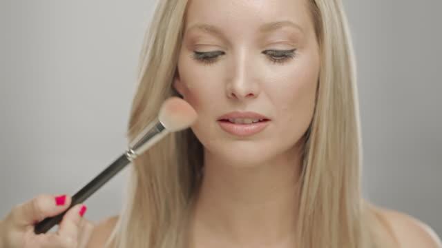 vídeos y material grabado en eventos de stock de makeup artist applying blush to cheek of woman - esmalte de uñas rojo