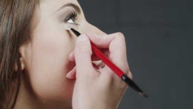 stockvideo's en b-roll-footage met cu makeup artist applying eye liner on woman's eye / orem, utah, usa - orem utah