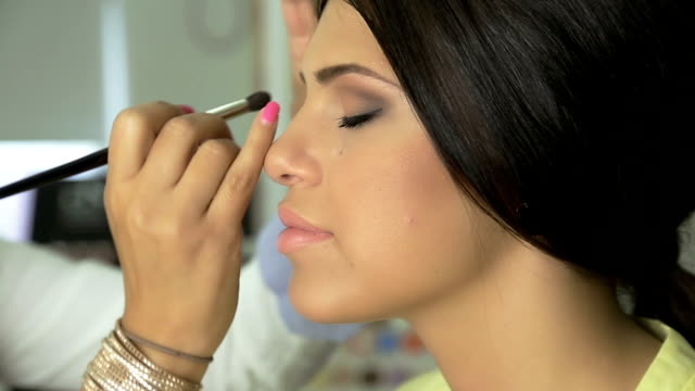 makeup artist applying  eye shadow on beautiful  young model - artist's model stock videos and b-roll footage