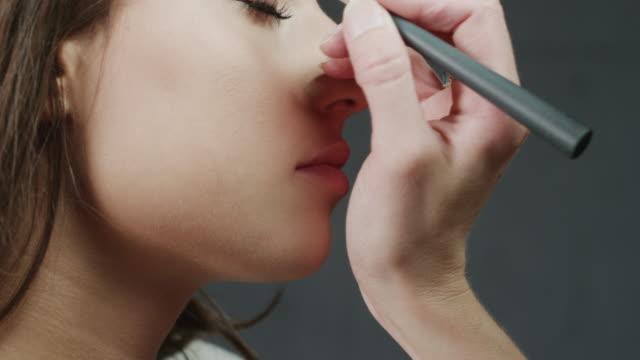 stockvideo's en b-roll-footage met cu tu makeup artist applying eye shadow on woman's eye / orem, utah, usa - orem utah