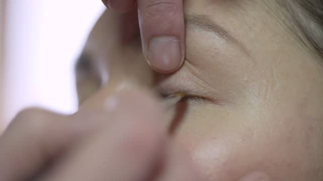 a make-up artist applying eyeliner to a models eyelid - eyelid stock videos and b-roll footage
