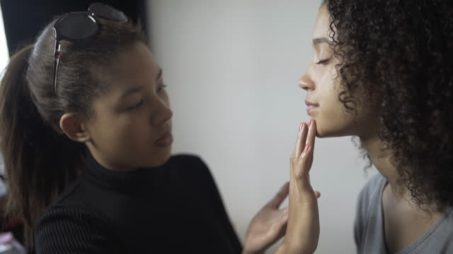 A make-up artist applying foundation.