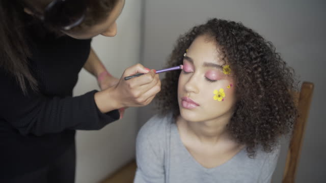 A make-up artist applying pink eyeshadow.
