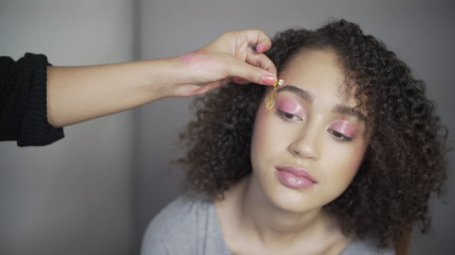A make-up artist applying pink flowers for a spring summer look.