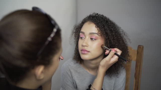A make-up artist applying Pink rouge