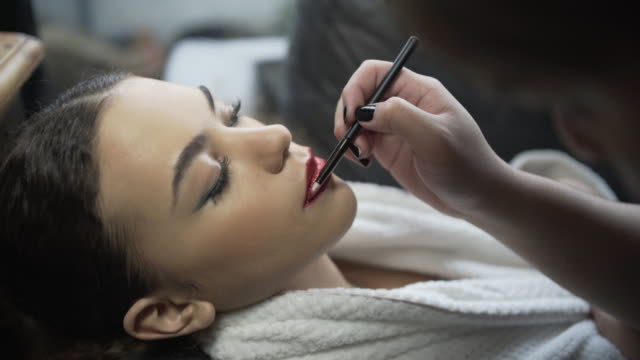 A make-up artist applying red glitter to a models lips.