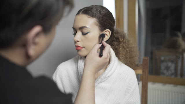 A make-up artist applying the finishing touches to a look BTS.