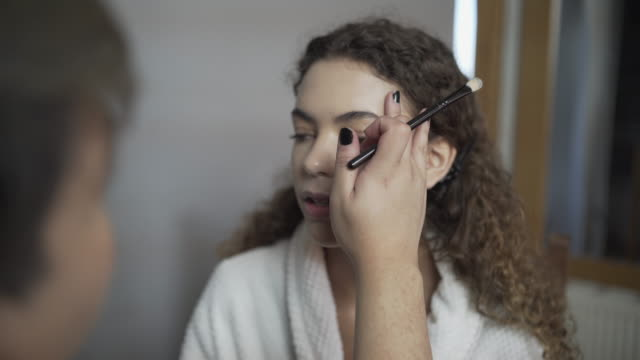 A make-up artist applying the first stages of foundation to a models face.
