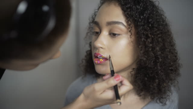 a make-up artist applying tiny real flowers to the lips of a model. - ビフォーアフター点の映像素材/bロール