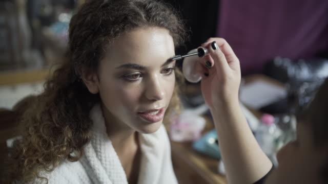 vídeos de stock e filmes b-roll de a make-up artist brushing a models eyebrows. - depilação