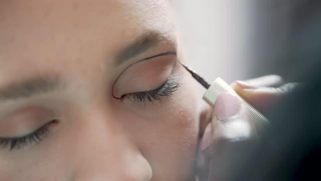 vídeos de stock, filmes e b-roll de um maquiador aplicando cuidadosamente um delineador gráfico a um rosto modelo - sobrancelha