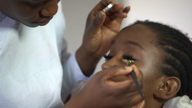 a make-up artist carefully applying gold paint to a models false eyelashes. - eyelash stock videos & royalty-free footage