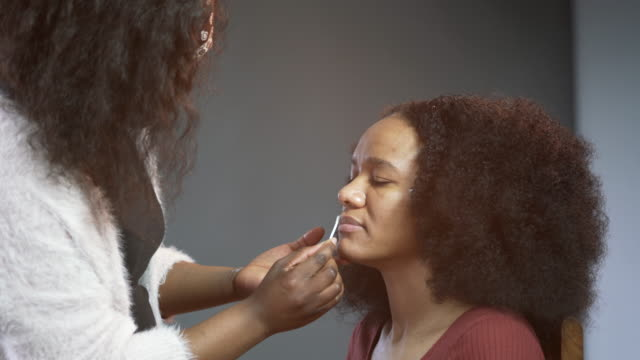 a make-up artist cleaning a models lips - cotton bud stock videos & royalty-free footage