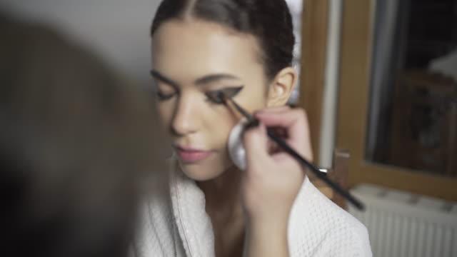 A make-up artist creating a dark black eyeshadow.