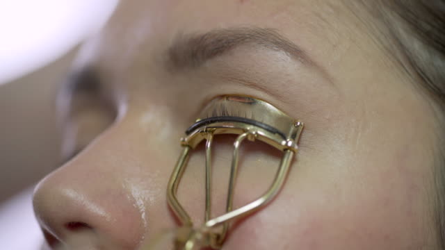 a make-up artist curling a models eye lashes. - eyelash stock videos & royalty-free footage