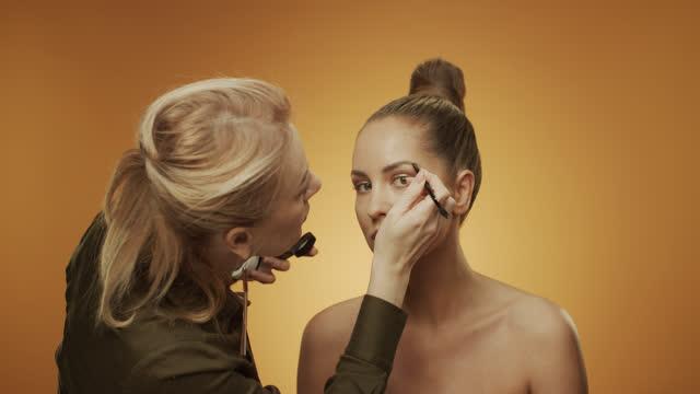 vídeos de stock, filmes e b-roll de maquiadora pinta as sobrancelhas do modelo com um pincel de maquiagem. - sobrancelha
