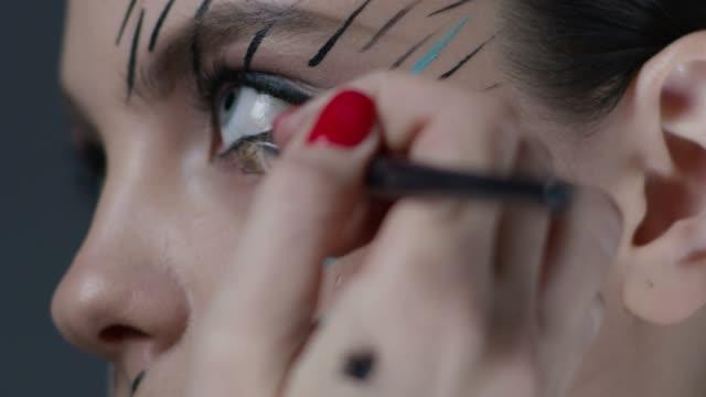 vídeos de stock, filmes e b-roll de make-up artista coloca uma maquiagem no rosto do modelo. nos bastidores. vídeo de moda. - maquiagem para teatro