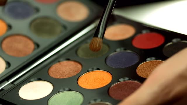 vídeos y material grabado en eventos de stock de hd: paleta de sombra de ojos con maquillaje artista - sombreador de ojos