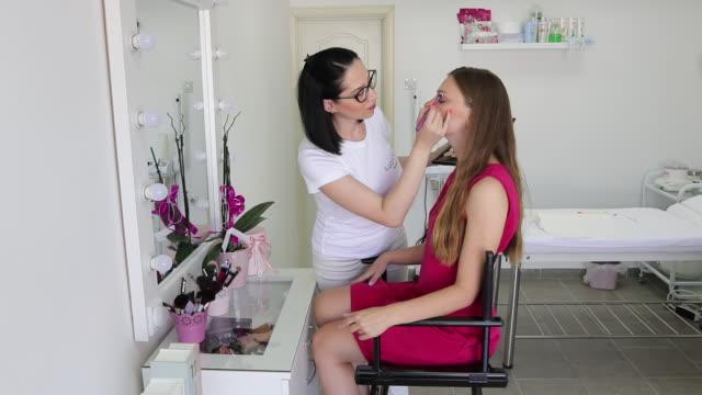 vidéos et rushes de maquilleuse travaillant au salon de beauté de son - se faire dorloter