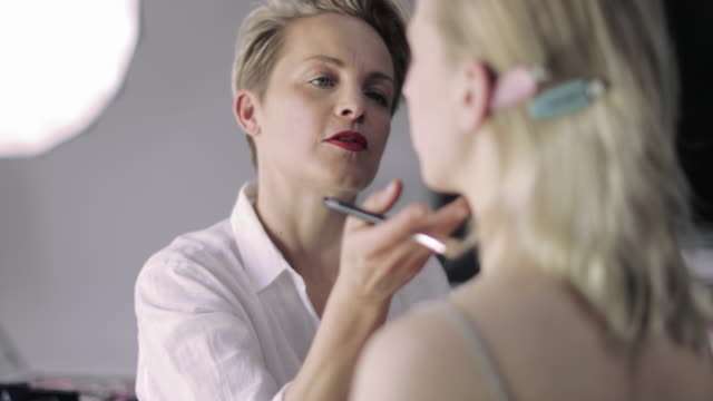 makeup artist working on a model on a photoshoot - catwalk stock videos & royalty-free footage
