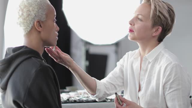 vídeos de stock, filmes e b-roll de makeup artist working on a model on a photoshoot - sobrancelha