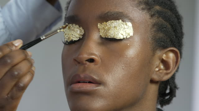 a make-up artist working with a model in the studio - gold leaf stock videos & royalty-free footage
