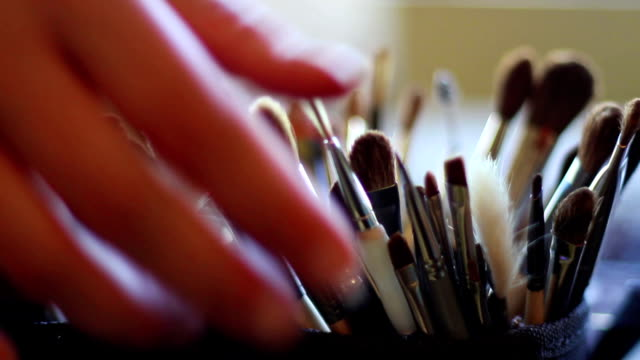 Makeup Artist's Hand Grabbing a Brush from Her Collection