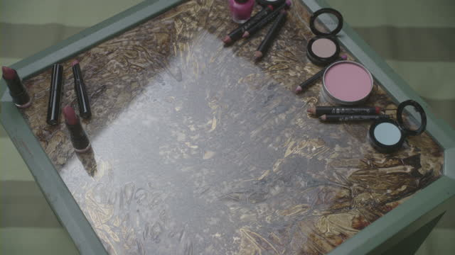 Makeup artists pick and choose cosmetics from a makeup tray.