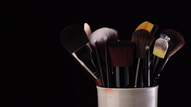 vidéos et rushes de brosse de maquillage dans la cuvette tournant sur le fond noir - pinceau à blush