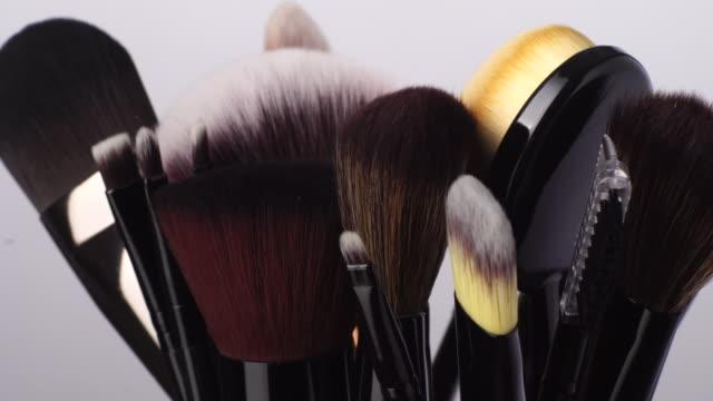 vidéos et rushes de brosse de maquillage dans la cuvette tournant sur le fond blanc - pinceau à blush