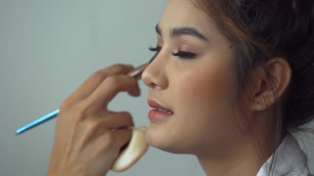 makeup routine and  beauty salon -  women face powders and apply blush to the cheekbones  to be highlighted - make up brush stock videos and b-roll footage