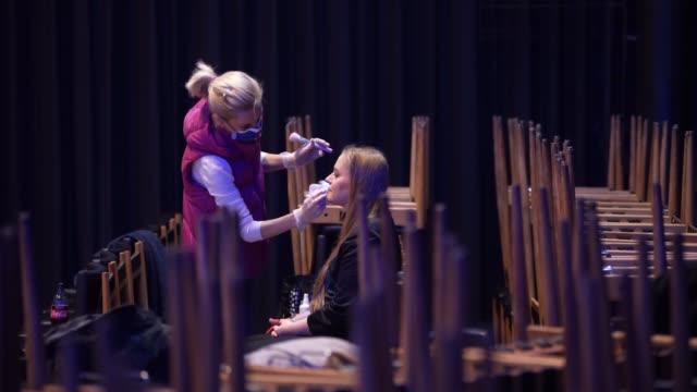 make-up specialist wearing a protective mask and gloves prepares singer soloist dana hoffmann for an interfaith church service among stacked chairs... - soloist stock videos & royalty-free footage