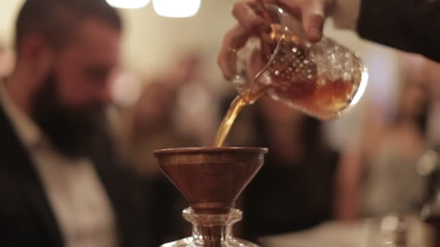 making a cocktail - pouring the cocktail into a smoked decanter - decanter stock videos & royalty-free footage