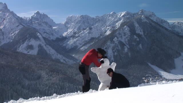 hd time-lapse: making a snowman - making a snowman stock videos & royalty-free footage